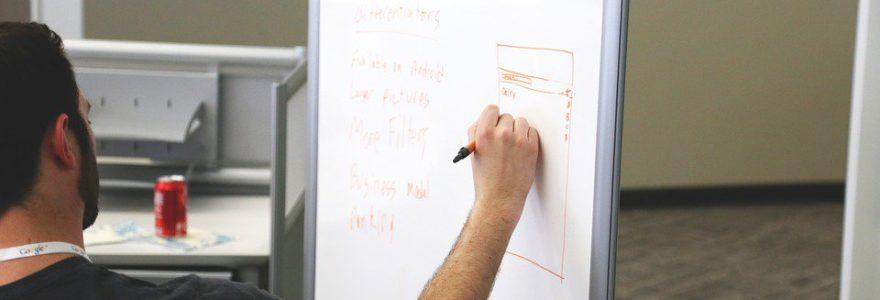 Personne écrivant sur un tableau pour planifier la gestion de projet